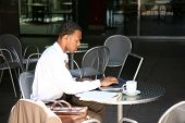 a business man works from his office at an outdoor coffee shop with his laptop and wireless internet