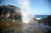 a blow hole on the island of maui in hawaii sends burst of water high into the air