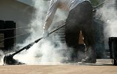 foto of tar  - a worker mops out molten tar on a roof replacement job - JPG