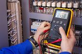 Multimeter In Hands Of Electrician Engineer In Electrical Cabinet. Maintenance Of Electric System. W poster