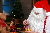 Santa in his workshop making new toys for Christmas Presents for children around the world
