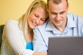 Jovem casal atraente usando Laptop.