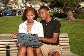 ein junges Paar Afroamerikaner sind schockiert, was sie sehen, während mit einen Laptop-Computer außerhalb