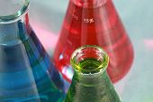 scientific and medical research beakers filled with various experiments with various colors and text