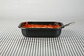 Hot fresh from the Microwave oven a Lasagna tv dinner sits on a black and white background waiting t