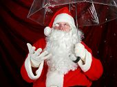 Santa Claus holds his transparent umbrella and checks for signs of snow before he goes to work on De