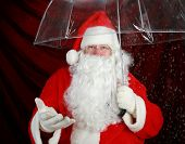 stock photo of 24th  - Santa Claus holds his transparent umbrella and checks for signs of snow before he goes to work on December 24th Christmas Eve - JPG