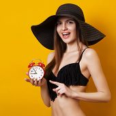 Beautiful Sexy Woman In Swimsuit With Alarm Clock Over Yellow Background. Seductive Girl Pointing On poster