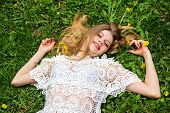 Cute Girl With Bliss Lying On The Green Lawn. poster