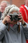 Old Paparazzi: an old woman taking photos with a retro camera.