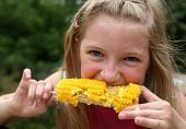 stock photo of sweet-corn  - Young funny girl eating a boiled corn - JPG