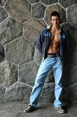 Muscular male torso in an undone jacket in front of the stonewall
