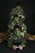 foto of video game controller  - Three brothers in camo paint and fatigues playing video games - JPG