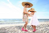 Two small girls dancing at the sunny beach. Shoot against the sun.