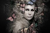 picture of black curly hair  - Beautiful young woman with butterfly in big curly hair on black - JPG