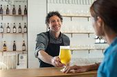 Happy bartender serving draught beer to woman at counter in restaurant. Smiling man behind countergi poster