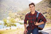 Young Hispanic man smiling during mountain hike, portrait poster