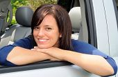 Happy Smiling Young Woman Sat In The Drivers Seat of Her Car