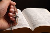 stock photo of holy-bible  - holy bible open with a cross on a hand - JPG