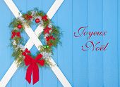 Christmas wreath hanging on a blue barn door with text Joyeux Noel, Merry Christmas in French
