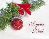 Red Christmas ball ornament with a heart and text Joyeux Noel, Merry Christmas in French