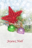 Dreamy image of colorful Christmas decorations in snow, with text Joyeux Noel, Merry Christmas in Fr