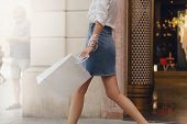 Crop Picture Of Girl Walking With Shopping Bag On City Streets While Doing Shopping. Stylish Girl Wa poster