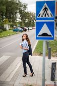 Beautiful Young Businesswoman Crossing A Street On A Pedestrian Cross At Daytime poster