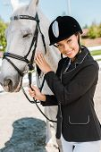 Attractive Female Equestrian In Riding Helmet Looking At Camera Near White Horse At Horse Club poster