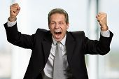 Excited Caucasian Businessman Celebrating Victory. Lucky And Happy Entrepreneur Raised Fists In Exci poster