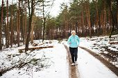 Happy Senior Woman Jogging In Winter Nature. poster