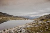 Rugged Dramatic Mountain Landscape In Norway Cloudy Dramatic Day Autumn With A Calm Lake Beauty poster