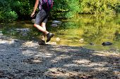 Hiking Shoes On Hiker Outdoors Walking Crossing River Creek. Woman On Hike Trekking In Nature. Close poster