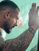 Man Latin With Muscular Body Looks Through A Broken Window. Brutal Handsome Man With Tattooed Body.  poster