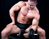 stock photo of bulge  - Man on bench with a bar weights in hands training - JPG