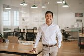 Young Asian Businessman Standing In An Office Smiling Confidently poster