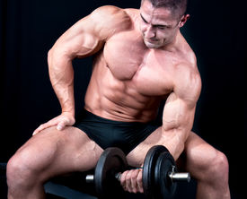 stock photo of body builder  - Man on bench with a bar weights in hands training - JPG