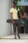 A Young Male With Skateboard And Bag