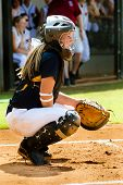 stock photo of infield  - Young teen girl playing softball in organized game - JPG