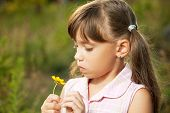 Cute Little Girl Playing With A Flower