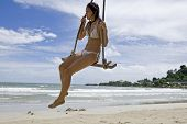 Girl On Swing On The Beach