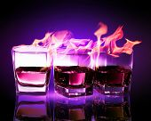 pic of absinthe  - Image of three glasses of burning puple absinthe - JPG