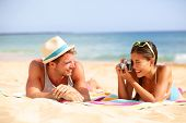Beach fun couple travel. Woman taking photo picture of man smiling happy with retro vintage camera,