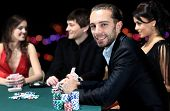 foto of gambler  - Poker players sitting around a table at a casino - JPG