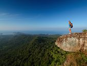 picture of breathtaking  - Lady with backpack standing by an edge of a cliff and enjoying valley view - JPG