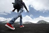 Hiker with backpack crossing valley covered with ash towards volcano