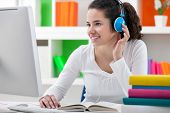 teen girl doing her homework online and listening to headphones.
