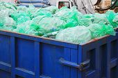 stock photo of dumpster  - Dumpster container with green bags for recycling - JPG