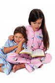 Girl Reading Bedtime Story To Sister