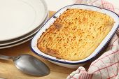 Homemade cottage pie, made with finely chopped cooked meat, onion and carrot, topped with mashed potato and baked until golden.